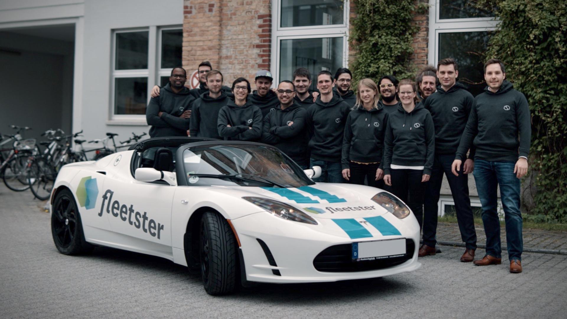 fleetster team posing in front of the Tesla roadster