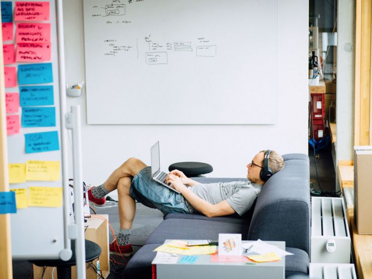 Bild eines Mitarbeiters mit Kopfhörern auf der Couch