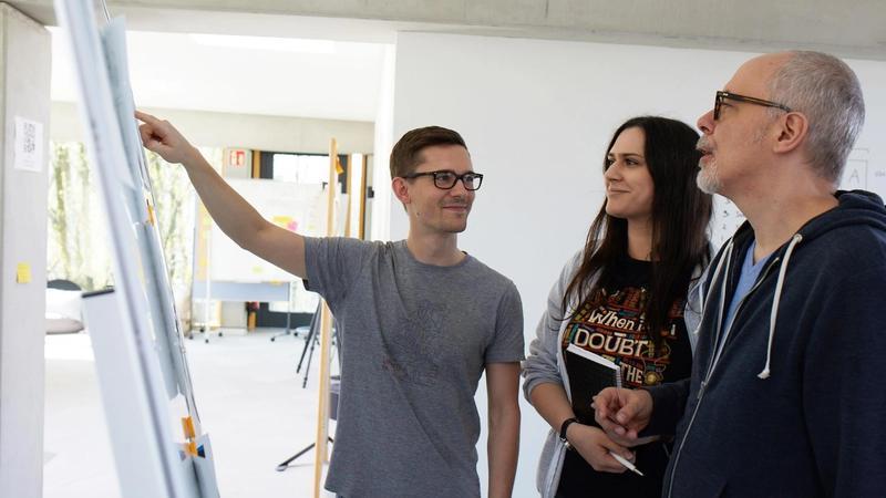 Bild mit Mitarbeitern an einem Whiteboard