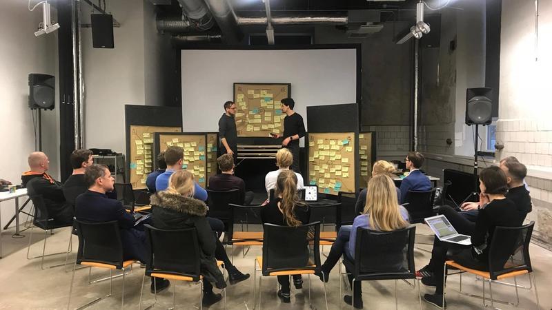 BIld eines Workshops mit Teilnehmern im Stuhl-Halbkreis versammelt
