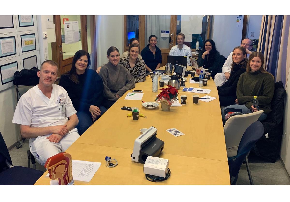 En gruppe med smilende kvinner og menn i sykehusuniformer samlet rundt et stort bord.