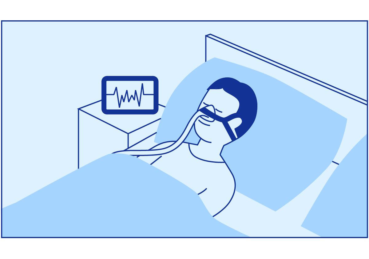 Pasienten sover hjemme i sin egen seng mens han har pustemaske på og det står en maskin på nattbordet hans.