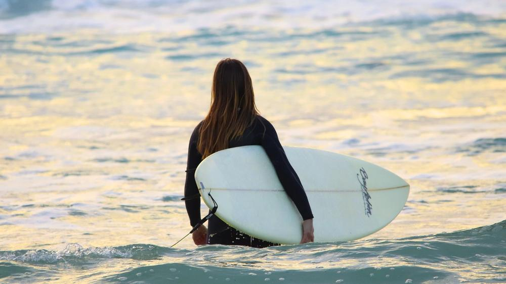 Person with long hair holding a white surfboard, looking out into the ocean.