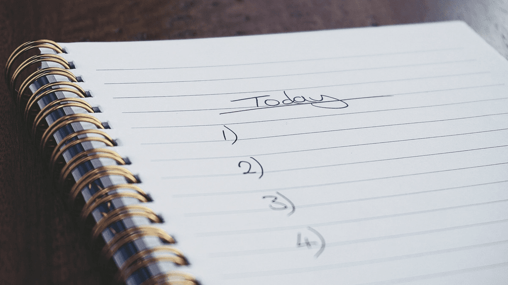 Image of daily plan being created in notebook; Photo by Suzy Hazelwood from Pexels