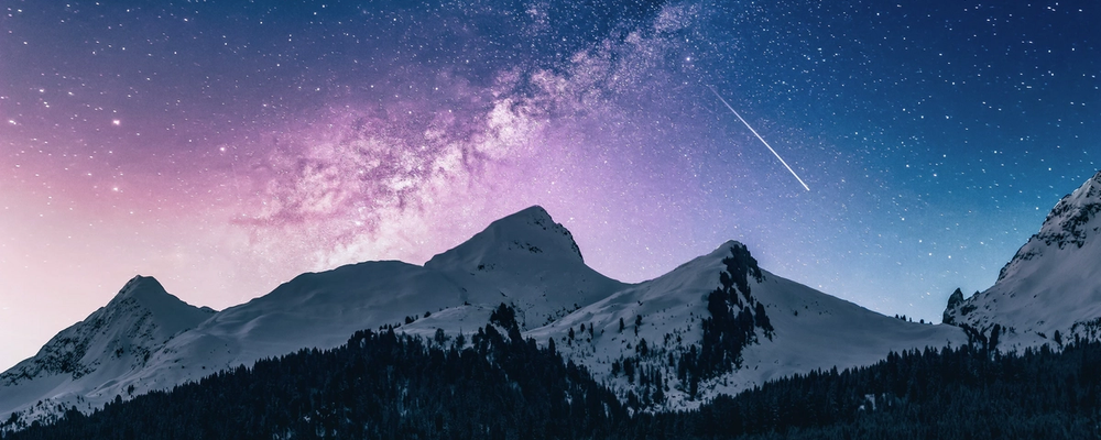 Range of mountains with stars at night