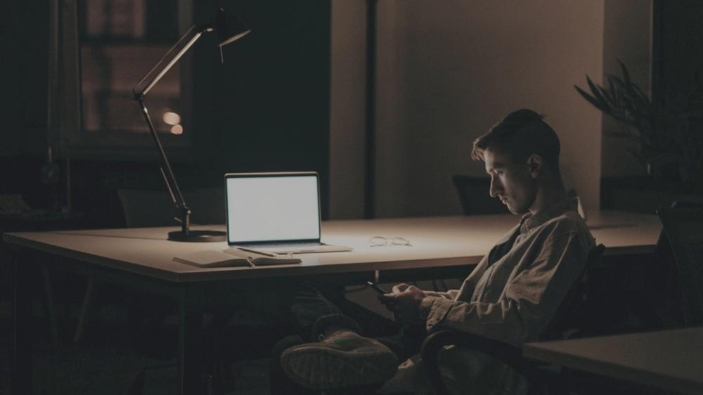 Man working late at desk (Photo by cottonbro)