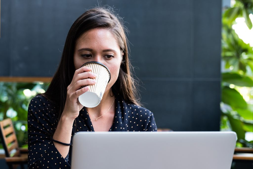 Woman working at computer on job CV with coffee - Image - She Mentors