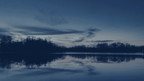 A sunset reflected on the lake, dark blue overlay