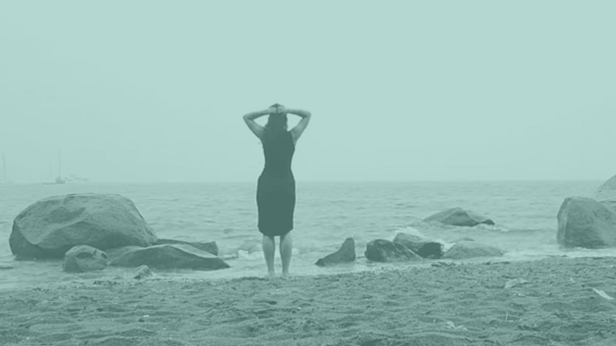 A woman on the beach facing the water with her hands on her head