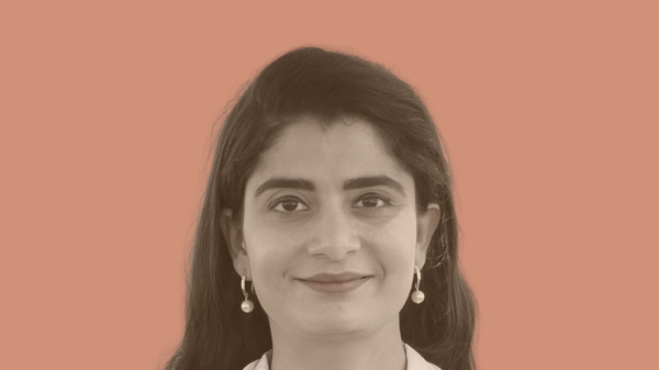 A person with long dark hair in a doctor's coat with earrings and a polka-dot shirt