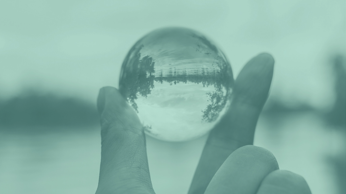 A photo of fingers holding a crystal ball