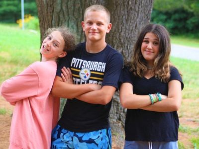 three members of the SIT Program at Camp Laurelwood, smiling at the camera