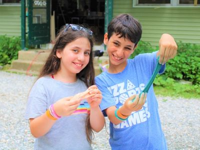 two smiling campers playing with silly putty at Camp Laurelwood