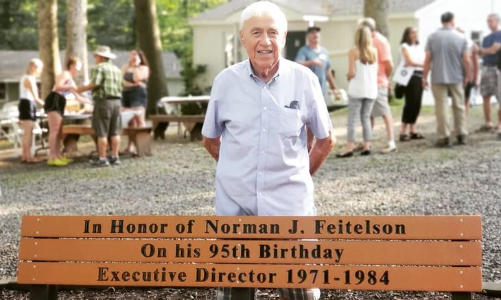 Laurelwood Alumni in front of sign reading 'in Honor of Norman J. Feitelson, on his 95th Birthhday, Executive Director 1971-1984