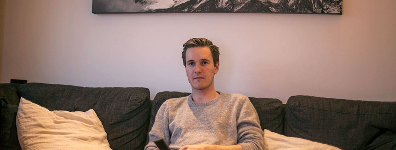 Simen Viste holder sitter i sofaen med fjernkontroll i hånda