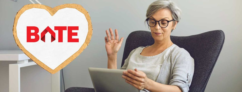 Dame som sitter i en stol og rekker hånden i været, deltar på digitalt møte