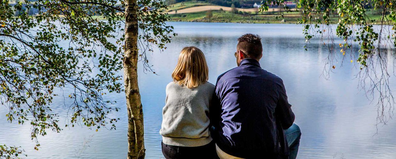 Par sitter på stubbe og ser utover Frøylandsvannet på Hommersåk