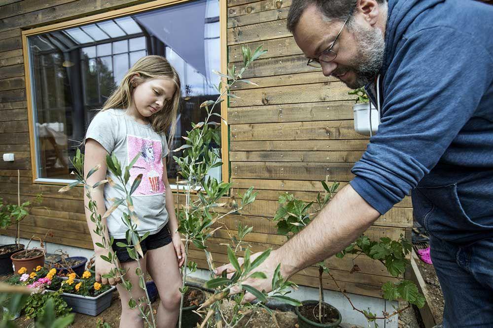 mann og en liten jente jobber i drivhus