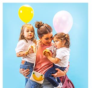 dame med to barn som holder ballonger