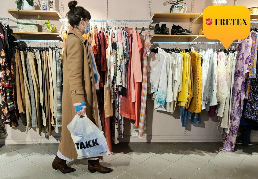 Dame i kåpe handler hos en fretex butikk