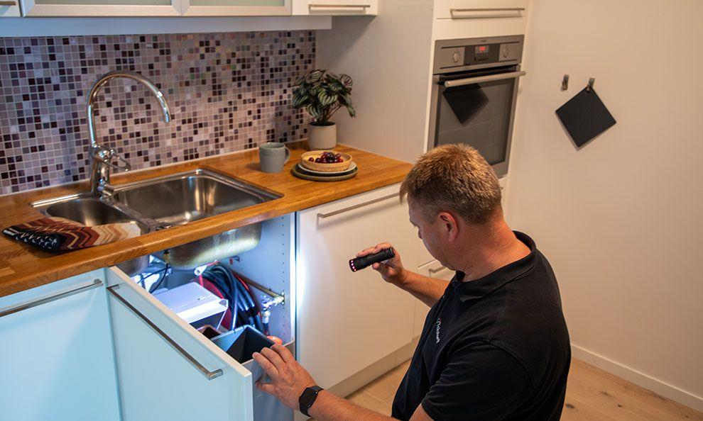 Takstmann sjekker under kjøkkenvasken