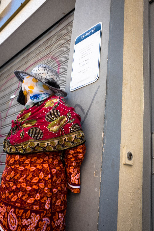 Frau mit buntem Kleid lehnt sich an Mauer in Marseille