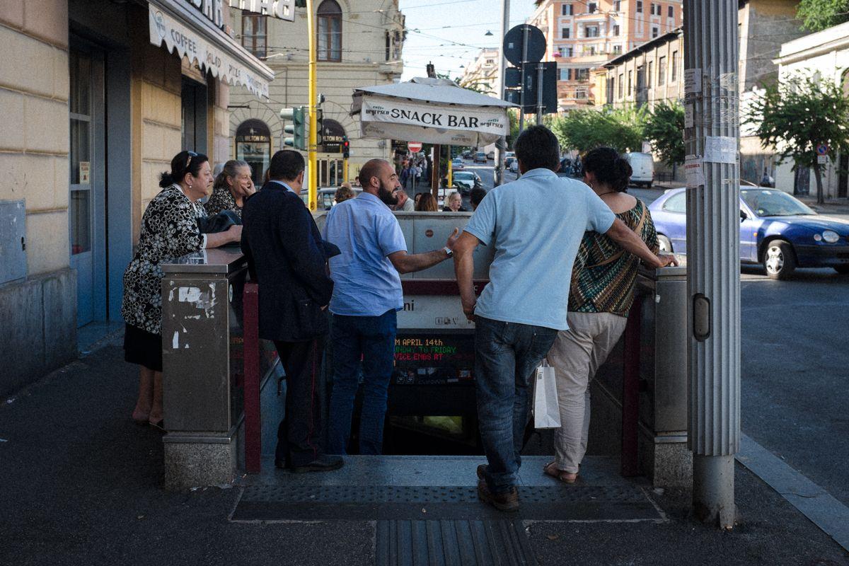 diskutierende Passanten am Eingang zur Metropolitana di Roma