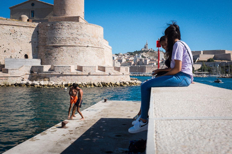 Streetphotography im Hafen von Marseille - Jugendliche sitzen auf der Kaimauer