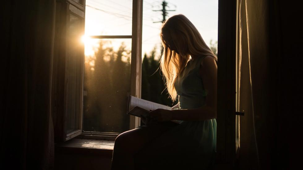 Woman reading in window