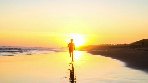 Mann løper på is i vakker solnedgang