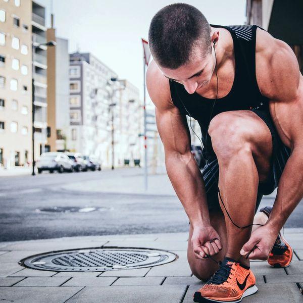Mann knyter joggeskoene på fortauet