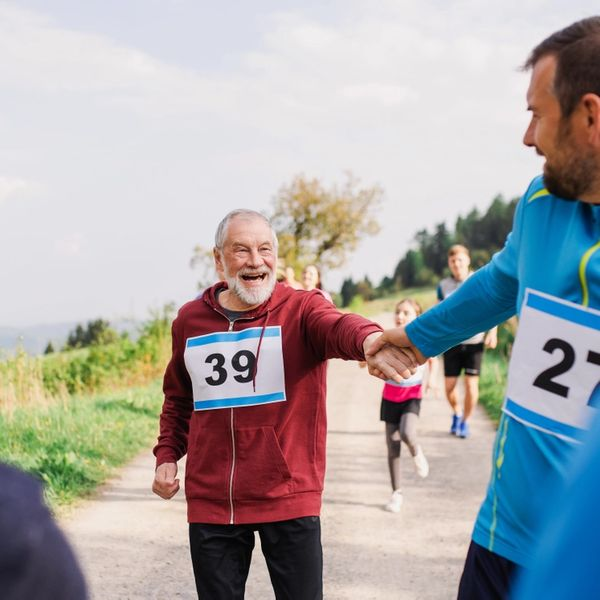 mann hjelper gammel mann med å holde følge