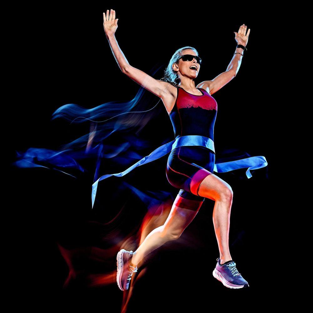 kvinne løper i mål med hendene i været