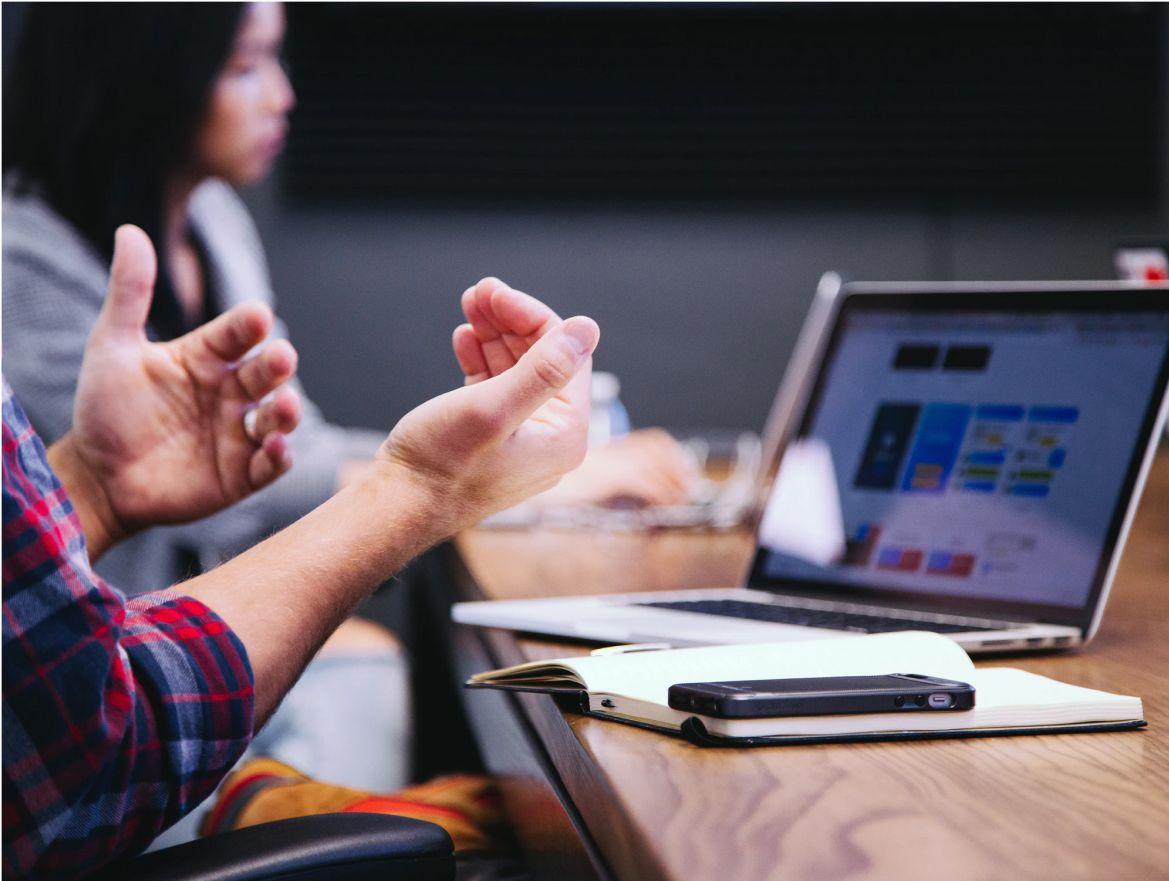 Manos de un hombre delante de un portátil y una libreta en una reunión de trabajo
