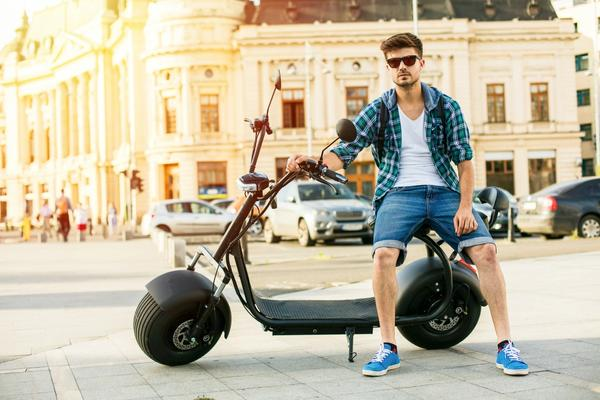 Man sitting on electric scooter in city center