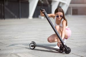 Woman folding the best foldable electric scooter.