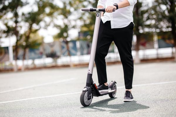 Lower body of a heavier person on an electric scooter.