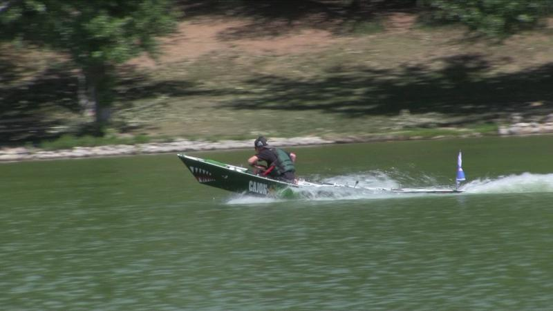 A racer flies through the water in a student-built speed boat.