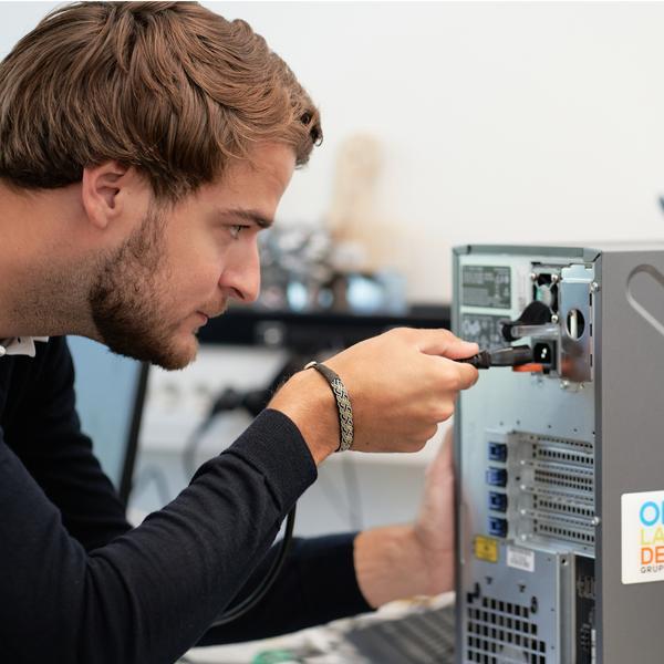 Person skruvar i en dator