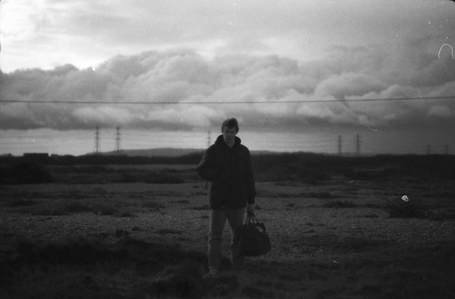 George MacKay stands against a storm cloud in Dungeness, the only desert in the UK.