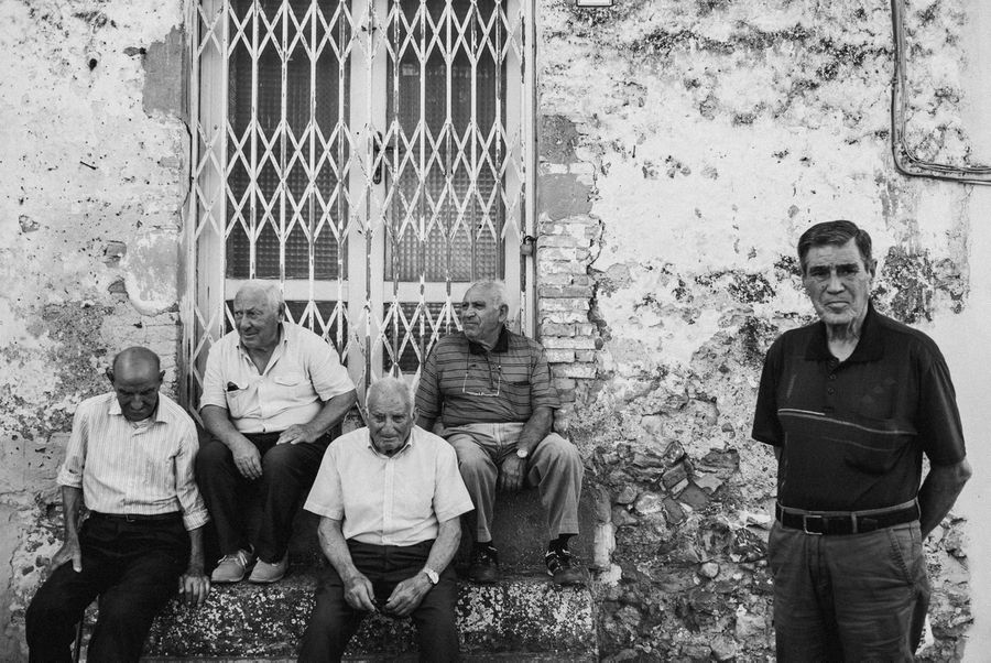 In black and white, four old men sit on the steps of an old Italian building. Another man stands closer to foreground avoiding eye contact with the camera.