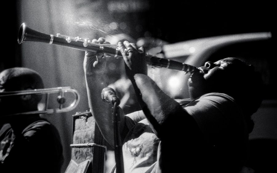 Woman playing clarinet in black and white. She blows hard arching her back as the instrument catches the sunlight.