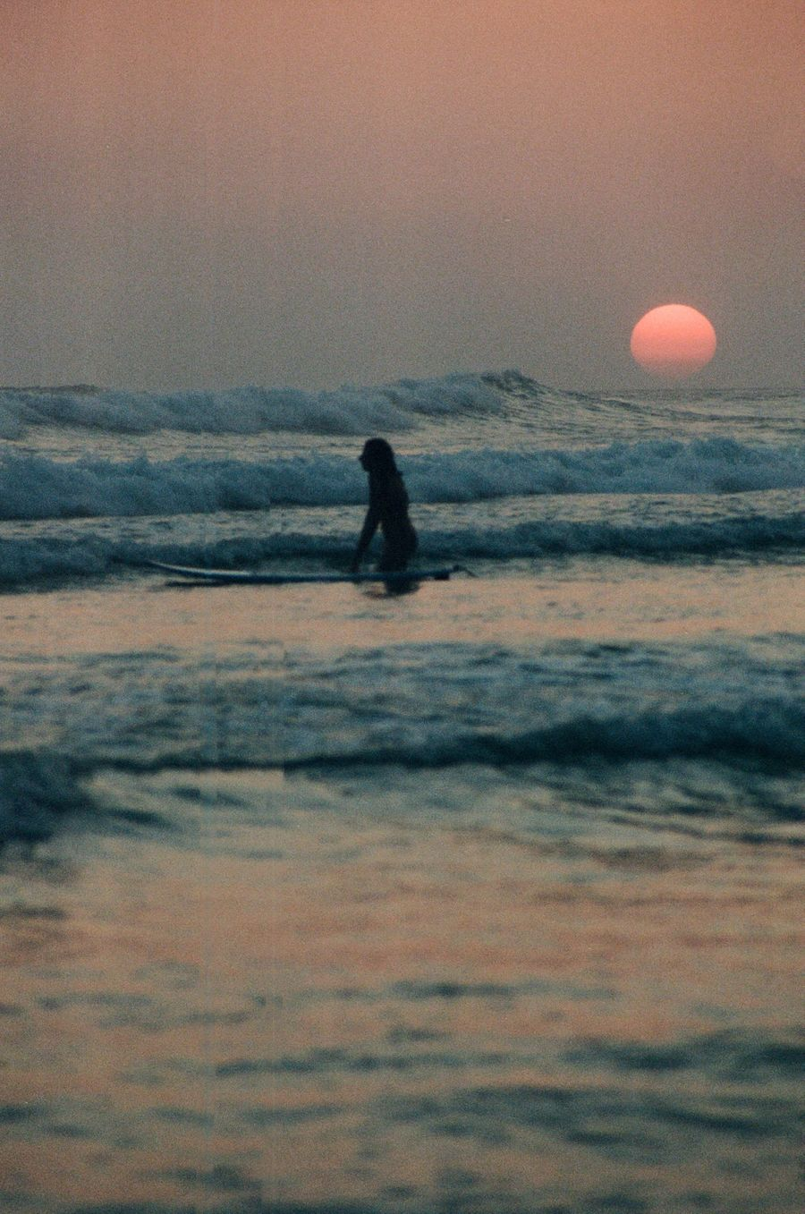 A telephoto shot of the pink red sun setting with a woman in foreground walking amongst the waves.