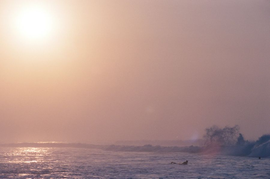 A surfer heads out towards the breaking waves. The early morning orange sun blends into the blue sea creating a purple gradient.