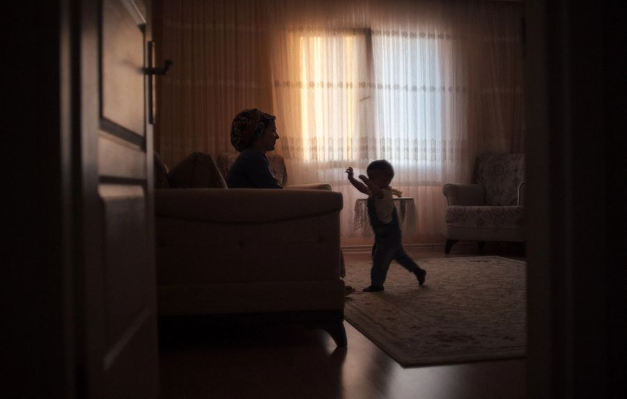 A two year old walks across the living room with his arms aloft ready to be caught by his mum sitting on the sofa. The sun is setting outside casting orange and blue hues onto the net curtain.