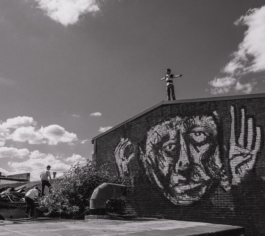 A boy stands with his arms aloft on top of a industrial building in hackney. The graffiti below him is of a man looking up worried. The boy's friends trail behind on their way up to the top.