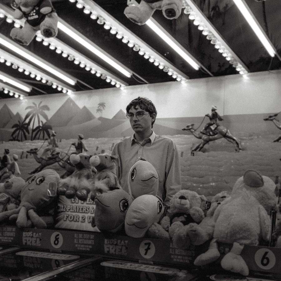 A teenage boy stands motionless behind an amusement ride looking glum. There's fun, lights and cuddly toys surrounding him.