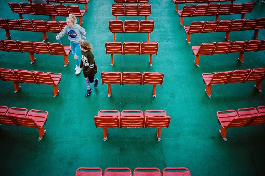 Looking directly down at the deck below with green floors and red chairs. Two kids run through the aisle.
