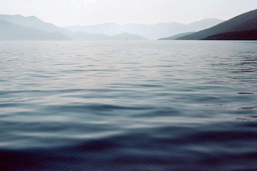Hazy blue morning on the Aegean Sea. Mountains and a small sailing boat in the distance. Gentle breeze over the water.
