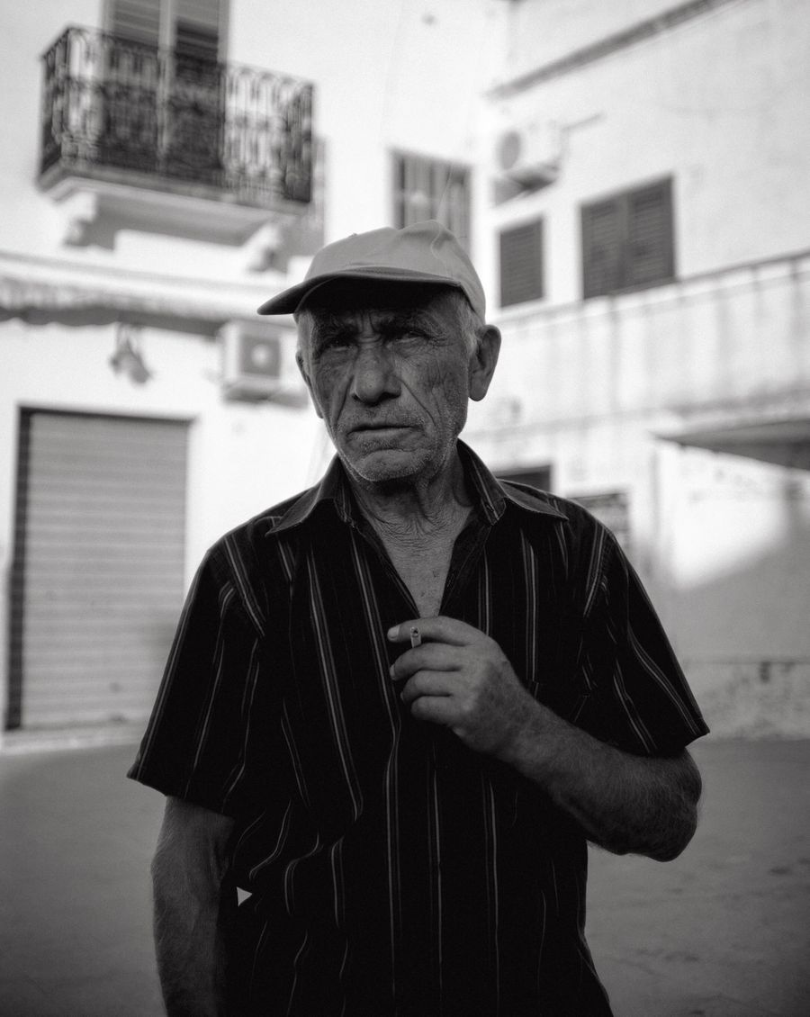 An old man looks directly down the lens as he pauses before taking a drag of his cigarette.